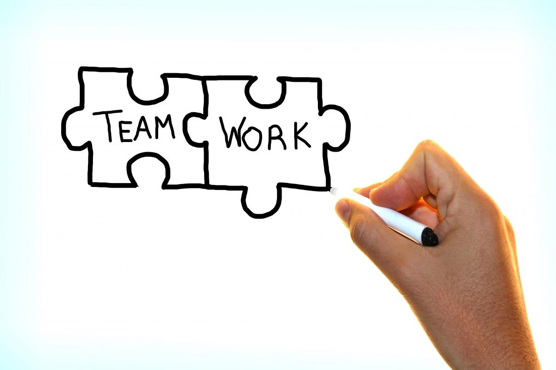 Hand writing the words Team Work on virtual screen